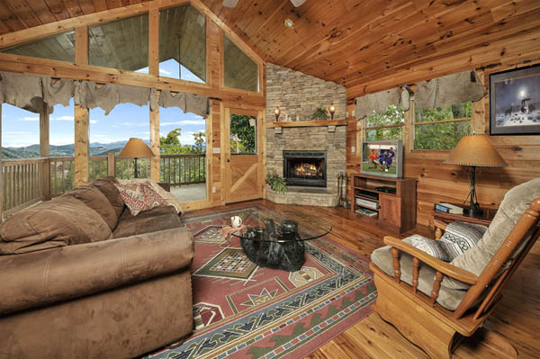 Living Room with fireplace and lots of glass looking out onto the Smoky Mountains view.